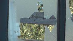 Broken glass windows with swaying trees in background, cut away shot Stock Footage