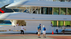 Tourists look at the luxurious yacht in the Caribbean sea port of San Martin Stock Footage