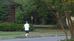Man jogging on suburban neighborhood street - stock footage