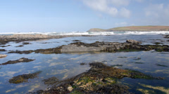Tide coming in over rock pools on beach, Constantine Bay, Cornwall, UK Stock Footage