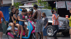 Young Women on a Motorbike Getting Mobbed During a Songkran Water Fight Stock Footage