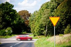 yield sign near crossroad and rushing car - stock photo