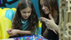Excited girl chats woman, plays board game, educational process - stock footage