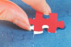 attaching the last red piece of puzzle - stock photo