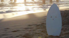 Sunset Skimboard with waves in background 720p Stock Footage