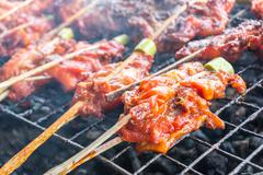 Grilled chicken thigh on the flaming grill Stock Photos
