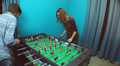 Beautiful girl young guy playing table soccer, chatting on date Footage