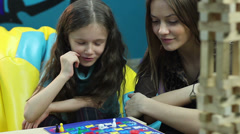 Excited girl chats woman, plays board game, educational process, click for HD Stock Footage