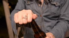 female opens beer bottle - stock footage