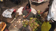 Woman peeling coconut with edge knife of south india Tamilnadu market Stock Footage