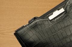 A black business bag on a wooden background - stock photo