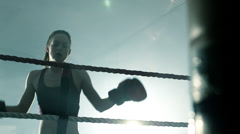 Female Boxer rests on the topes of the Ring, then turns to back to her fight. Stock Footage