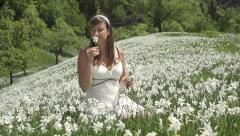 SLOW MOTION: Woman in white dress smelling flowers Stock Footage