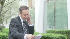 MS Business man recieves a call whilst Business Woman walks by Stock Footage