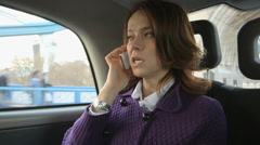 Business woman travels through the city in a taxi whilst making a business call Stock Footage