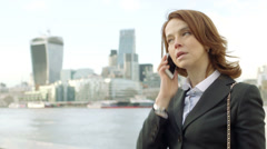 Woman outside offices in front of the River Thames on phone Stock Footage