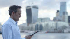 Business man uses his digital tablet/ipad in the city Stock Footage