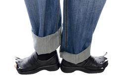 Feet in jeans and shoes on white Stock Photos