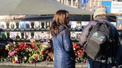 Two women look at memorial wall of slain ukrainian protesters Stock Footage