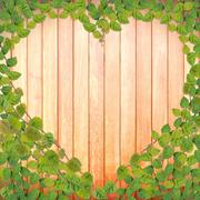 green creeper plant shaped as heart on wood plank - stock illustration
