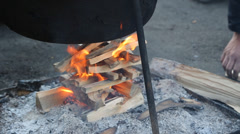Open air fire under cast iron cooking pot Stock Footage