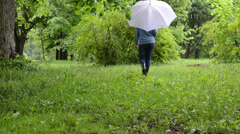 Woman with umbrella and gumboots walk between bushes and trees Stock Footage