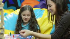 Smiling girl plays board game sister, family bonding, education, click for HD Stock Footage