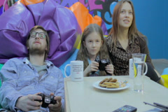 Family playing video game, gaming habit, time wasting, addiction, click for HD Stock Footage