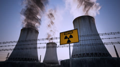 Nuclear power plant cooling towers. Caution sign barbed wire sunset - stock footage