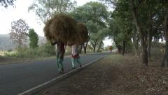 P03522 Women Carrying Load on Head Walking Highway Stock Footage