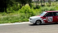 Two racecars approaching in hot pursuit, take turn, drive away Stock Footage