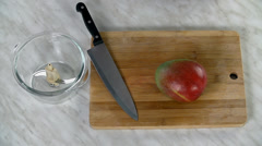 Cutting up mango in slow motion Stock Footage