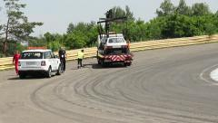Evacuator removes broken racing auto from track, crew leave road Stock Footage