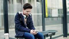Young teenage boy texting on smartphone, waiting for bus HD - stock footage