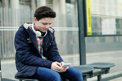 Young teenage boy texting on smartphone, waiting for bus NTSC - stock footage