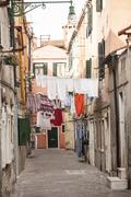 Laundry hanging over village street Stock Photos