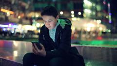 Young teenager texting on smartphone in the city at night HD Stock Footage
