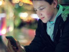 Young teenager texting on smartphone in the city at night NTSC Stock Footage