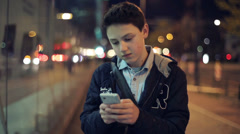 Young boy with smartphone stand by the bulding in the city HD Stock Footage