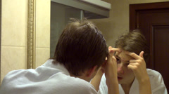 Teenage boy with acne squeezing out pimples on face looking in mirror at zits Stock Footage