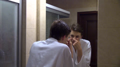 Teenage boy, skin care, dermatology, poking a pimple, puberty Stock Footage