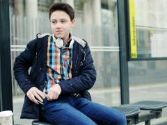 Young teenager waiting for bus on bus stop in the city NTSC Stock Footage
