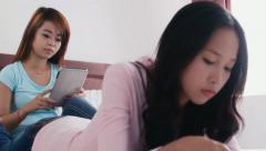 7of13 asian girls using ipad, phone and studying at home Stock Footage