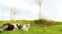 Relaxing outside with her Shih-Tzu dog - zoom dolly Stock Footage