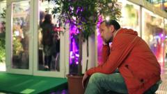 Sad man, uninvited to party sitting by entrance to night club HD Stock Footage