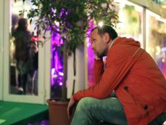 Sad man, uninvited to party sitting by entrance to night club NTSC Stock Footage