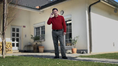 Father tries to make a telephone call in his yard - stock footage