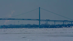 The Ambassador Bridge crossing over the ice covered Detroit River Stock Footage