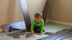 LITTLE BOY PUTTING WOOD FLOORING IN. Stock Footage