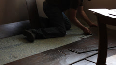 WORKER PUTTING IN NEW WOOD FLOORING Stock Footage